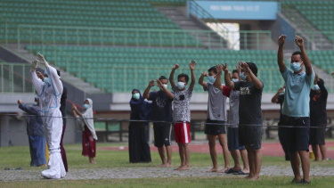 A health worker wearing protective suit performs exercise with patients at the Patriot Candrabhaga stadium outside Jakarta. The stadium was turned into an isolation centre for people showing symptoms of COVID-19.