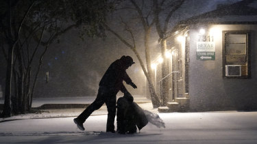 Two people play in the snow in San Antonio.