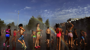 Children cool off in an urban beach at Madrid Rio park in Madrid.