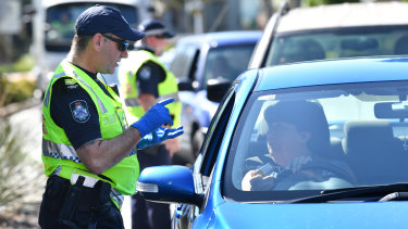 Police stop cars at a checkpoint on the Queensland and New South Wales border on Friday.