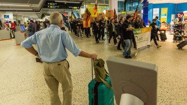 A passenger watches Jetstar workers and union officials at Melbourne Airport.