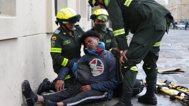 Police attend to an anti-government protester affected by tear gas during clashes in downtown Bogota, Colombia.
