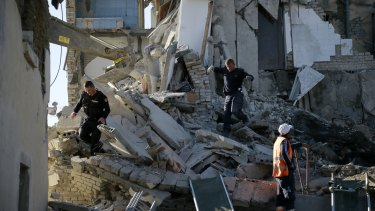 Rescuers search a damaged building after a magnitude 6.4 earthquake in Thumane, western Albania.