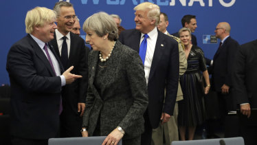 President Donald Trump jokes with British Foreign Minister Boris Johnson as British Prime Minister Theresa May walks past during a working dinner meeting at the NATO headquarters in May, 2017.