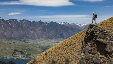 A hiker looks over Lake Wakatipu to the Remarkables on New Zealand's South Island.