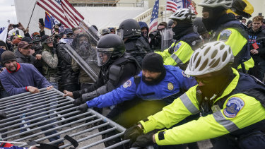 Conspiracy theories go kinetic: Trump supporters beat down barricades and attacked police in a violent riot on January 6 before breaching the Capitol building itself.