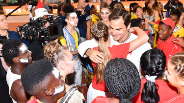 Roger Federer hugs young fans after defeating Rafael Nadal at Cape Town Stadium.