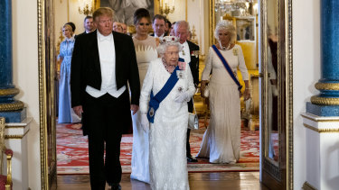 Trump and first lady Melania Trump walk with the Queen.
