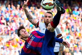 Lionel Messi tussles with Valencia's Nicolas Otamendi during a 2015 La Liga clash.