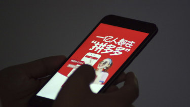 A Chinese customer uses the mobile app of Chinese e-commerce platform Pinduoduo on his smartphone.