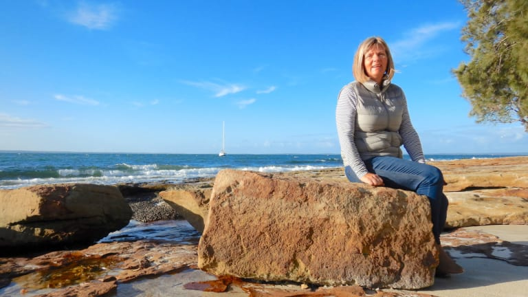 Jenny Robertson sits on an old sandstone block, a remnant of the South Huskisson wharf at the end of the Wool Road.