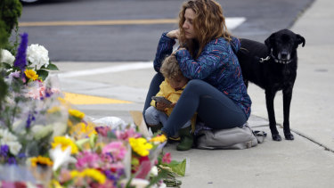 Ali De Leon and her son pause at a growing memorial across the street from the Chabad of Poway synagogue.