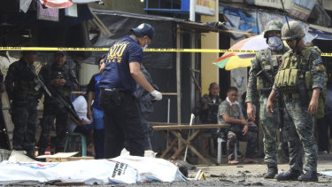 Police investigators examine the site after the January bombings in Jolo, Philippines.