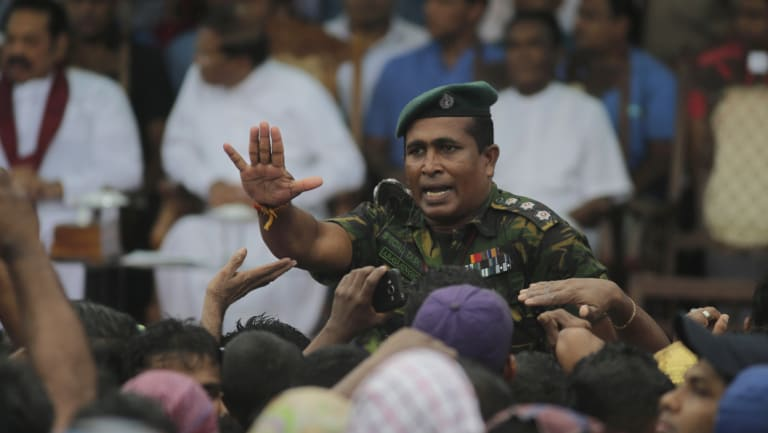 A Sri Lankan police officer tries to control supporters of Sri Lankan President Maithripala Sirisena at a Colombo rally last week.
