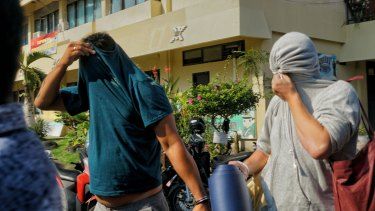 Australian nightclub promoters William Cabantog (blue shirt) and David Van Iersel (grey shirt) are transferred between cells at Denpasar police station.