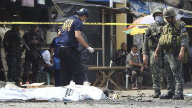 Police investigators examine the site after the bombings in Jolo, Philippines.