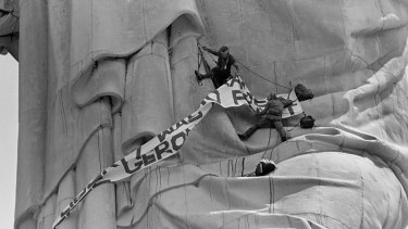 Edwin Drummond, top, and Stephen Rutherford climb a third of the way up the Statue of Liberty in New York Harbor.