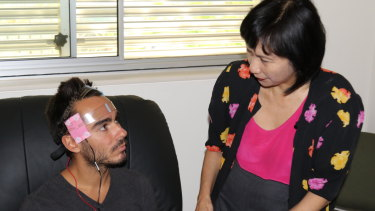 Professor Colleen Loo applies a transcranial direct-current stimulation device to an unnamed volunteer.
