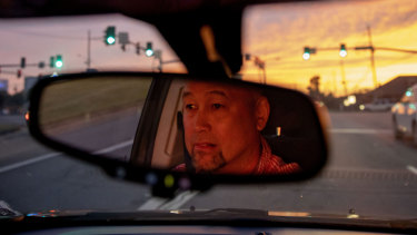 Robby Perez, who says in a lawsuit he was sexually abused by a priest when he was 11 years old in Guam, sits at a traffic light during sunset in New Orleans, where he now lives.