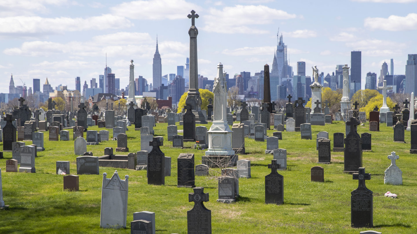 The Empire State building and the Manhattan skyline are seen behind the tombstones at Calvary Cemetery, Saturday, April 11, 2020, in the Maspeth neighborhood of the Queens borough of New York. The U.S. has recorded nearly 20,000 deaths from the coronavirus, overtaking Italy for the highest death toll in the world. Nearly half of the deaths in the United States happened in the New York state, but fear is mounting over the spread of the virus into the nation's heartland.