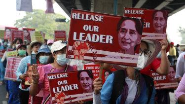 University teachers march with the images of deposed Myanmar leader Aung San Suu Kyi in Yangon, Myanmar, Friday, Feb. 26, 2021.