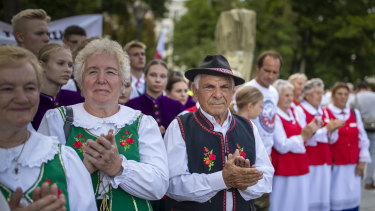 Protesters wearing traditional Lithuanian outfits attend an anti-migrant protest rally at the Vinco Kudirkos Square, in front of the government palace in Vilnius, Lithuania.
