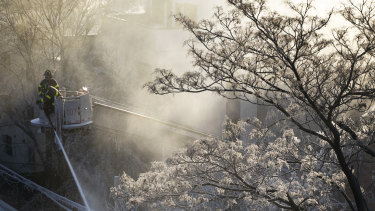 Ice forms on tree branches as New York firefighters battle a blaze in a commercial building.
