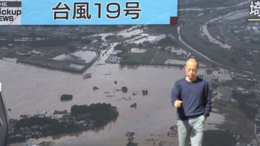 A man walks in front of huge TV screen showing a news program with footage of one of areas devastated by Typhoon Hagibis.