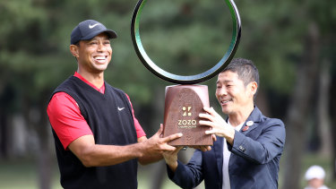 Golfer Tiger Woods receives the trophy from the Zozo founder Yusaku Maezawa at the Zozo Championship in Inzai, Chiba, Japan, last year.