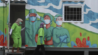 Health workers walk out of a mobile laboratory before analysing samples collected during mass coronavirus tests in Jakarta, Indonesia on Thursday.