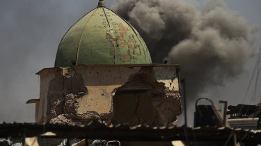 Smoke fills the air from an airstrike behind the historic Great Mosque of al-Nouri that was blown up by Islamic State militants as they retreated in Mosul in 2017.