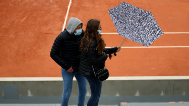 Fans head for shelter as rain falls during day one of the 2020 French Open at Roland Garros.