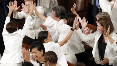 All in white in the house: Democrat congresswomen, including Alexandria Ocasio-Cortez, centre, cheer after President Donald Trump acknowledges more women in Congress during his State of the Union address.