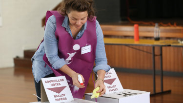 An election official sanitises the ballot boxes on polling day.