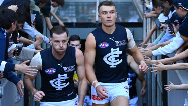 Sam Docherty and Patrick Cripps lead their team out on to the field during the round seven AFL match between the Bombers and the Blues.