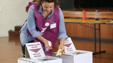 An election official sanitises the ballot boxes.