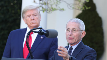 Dr Anthony Fauci, director of the National Institute of Allergy and Infectious Diseases, right, helped make the case for a longer shutdown to US President Donald Trump.