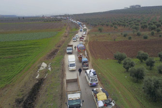 Civilians flee from Idlib to find safety inside Syria near the border with Turkey on Tuesday.