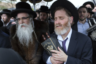 Community members, including Rabbi Chaim Rottenberg (left), celebrate the arrival of a new Torah near the rabbi's residence in Monsey, New York, a day after the knife attack.
