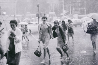 Soaked to the skin and past caring about the rain, these two girls splashed across Swanston Street to Flinders Street Station at the height of a torrential downpour,