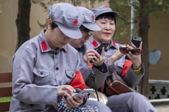 Chinese tourists dressed in Long March uniforms use technology that was beyond the wildest dream of Yan'an's revolutionaries.