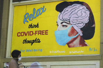 "A woman wears a face mask while walking under a sign that reads ""Relax think COVID free thoughts"" during the coronavirus outbreak in San Francisco."