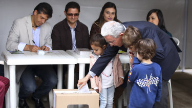 Former Colombian president Alvaro Uribe casts his ballot, accompanied by his grandchildren on Sunday.