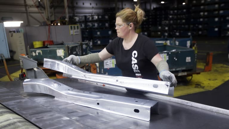 United Auto Workers line worker Crystal McIntyre unloads parts from a stamping machine at the General Motors Pontiac Metal Centre in Michigan.