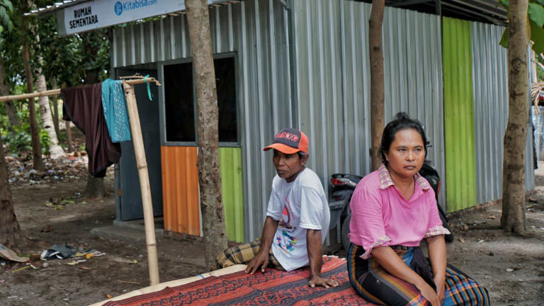 Ismail and his wife sitting in front of the temporary house built for them by an NGO.