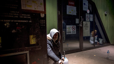 A man sits next to the needle vending machine outside the safe injecting room.
