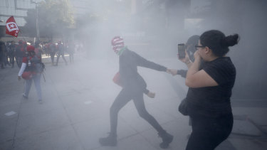Demonstrators are surrounded by a cloud of tear gas during an International Women's Day march in Mexico City.