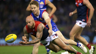 Dogged: Melbourne's Nathan Jones handballs on under pressure from Lachie Hunter.