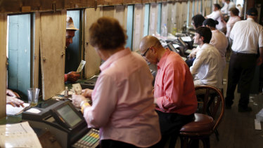 Workers take bets before the 144th running of the Kentucky Oaks horse race on May 4.