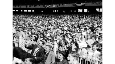 A sea of hats, suits and ties and best frocks. An immaculately dressed crowd watches the game.